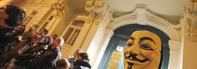 A man wearing an anonymous mask stands in front of the Hungarian embassy in Vienna