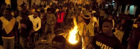 Anti-government protestors march past burning tyres in Dakar