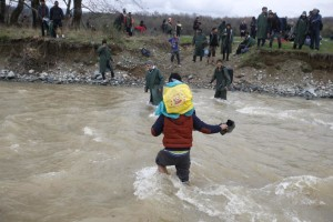 Migrants wade across a river near the Greek-Macedonian border, west of the the village of Idomeni March 14, 2016. REUTERS/Stoyan Nenov