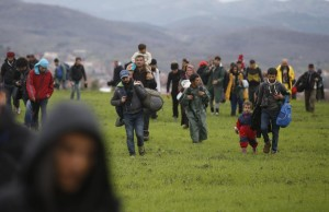 Migrants walk through a field looking for a way to cross the Greek-Macedonian border, near the village of Idomeni March 14, 2016. REUTERS/Stoyan Nenov