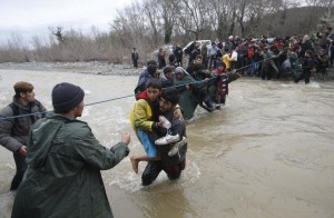 Migrants wade across a river near the Greek-Macedonian border, west of the the village of Idomeni, Greece, March 14, 2016. REUTERS/Stoyan Nenov